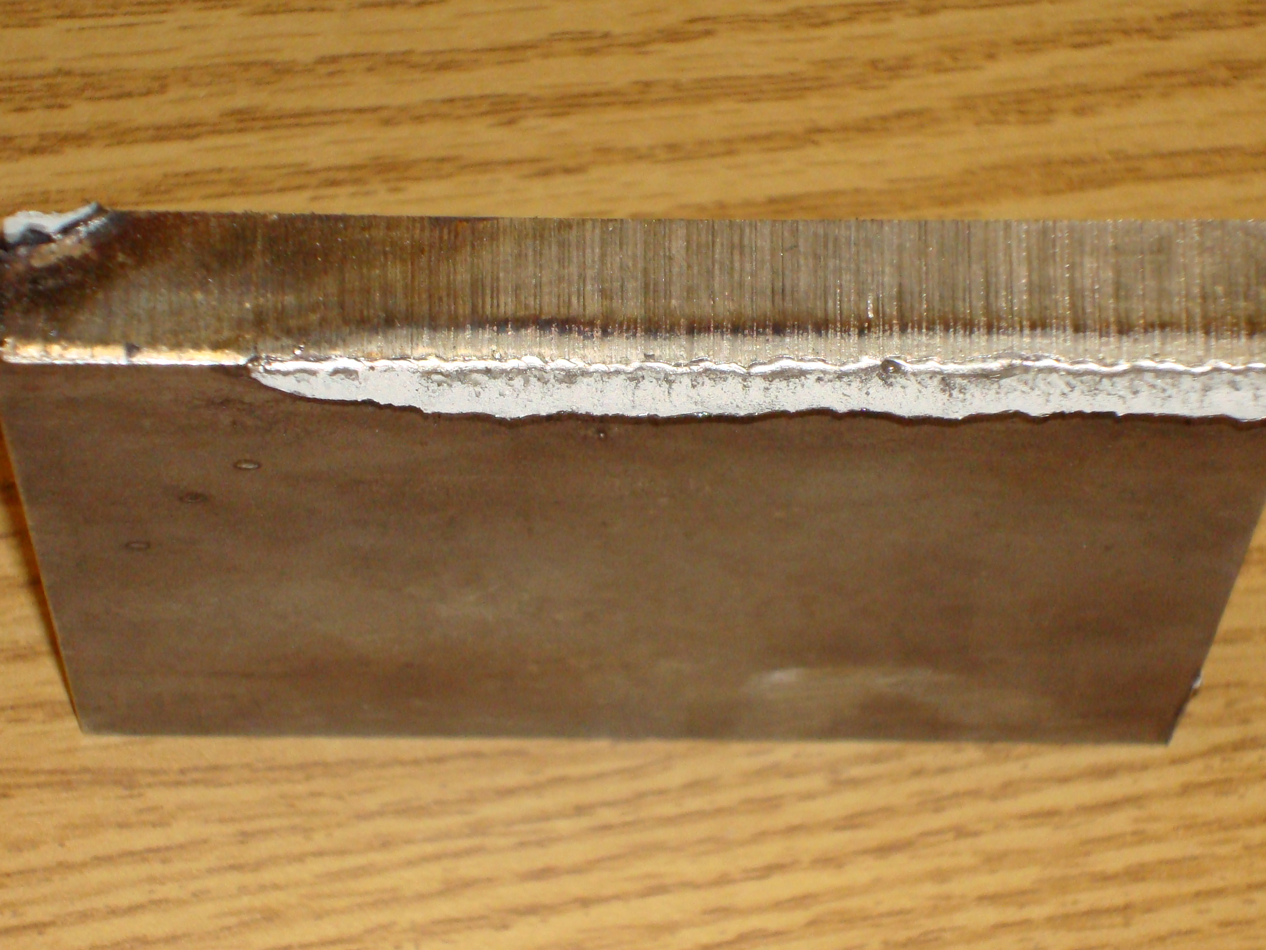 "Figure 2. The exposed edge of the vertical plate should have absolutely no sections of straightness on its edge, should appear to be wavy along the entire length, and should resemble a ""pore"" as shown here.(Click on photo to enlarge it)"