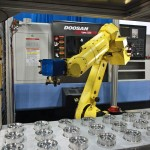 The DooCell manufacturing cell layout allows the robot arm to reach stock and parts in even the most remote sections of the pallet and does so without the need for cumbersome, maintenance-intensive drawers and trays. This compact design, when encased in a cage, measures 77 in x 77 in, excluding the machine tool. Equipped with either a Fanuc M10 or M20, the robot can lift parts up to 7 lb or 12 lb.(Click on photo to enlarge it)
