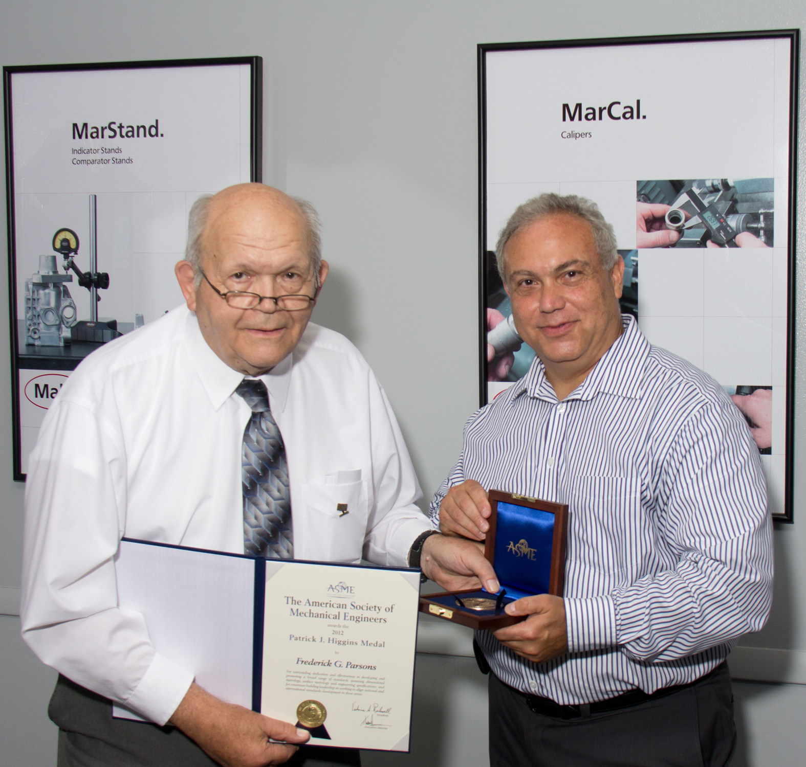 In a ceremony at the headquarters of Mahr Federal, long-time employee Frederick G. Parsons (left) is presented with the Patrick Higgins Medal by ASME's Steve Weinman in recognition for outstanding dedication and effectiveness in developing and promoting a broad range of standards in dimensional metrology, surface metrology and engineering specifications.(Click on photo to enlarge it)