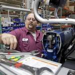 Systems electrical assembler Kevin Quick replaces the motor in an integrated reactor machine for spraying insulation at the manufacturing facility of Graco Inc. in Minneapolis, MN. (Photo courtesy of Ariana Lindquist/Bloomberg; click on photo to enlarge it)