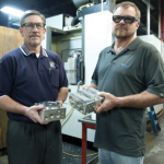 Brian Thoreson, machine shop supervisor (right) of Western Products and Michael Dulmes, Kurt sales representative (left) holding manifold blocks finished machined manifold block.(Click on photo to enlarge it)