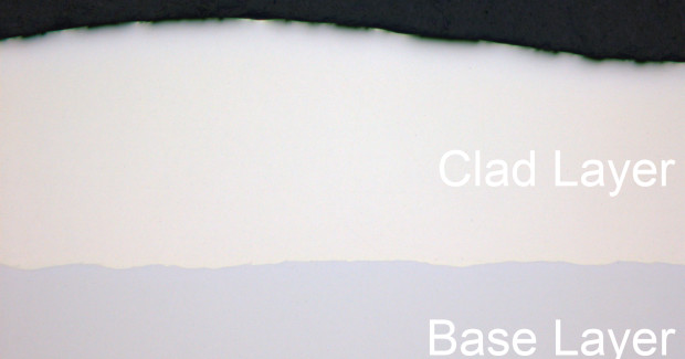 Cross section (not etched) of a high power diode laser clad coating (Coherent HighLight operating at 4 kW). The base substrate is a 0.2 percent carbon steel, while the clad is 309L austenitic stainless steel. Note the freedom from pores, cracks, bonding defects and other defects in the coating.