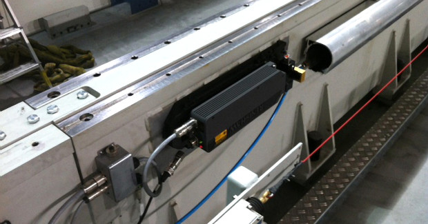 The HS10 laser encoder launches its beam down an air-purged duct near the drivetrain on the Composites Machining Center.
