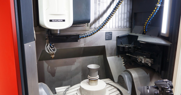 Laser metal deposition for additive manufacturing meets conventional metal cutting subtractive manufacturing on the same machine, run entirely by a single CNC in an inert atmosphere to make a turbine housing from titanium. (second view)