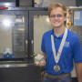 Greg Kersulis of Waterloo poses with his medal and a machinist cube made on a CNC machine tool recently at the SWIC Sam Wolf Granite City Campus Industrial Technology Center. Kersulis took second place in Precision Machining at the 2014 SkillsUSA Competition held in June in Kansas City.
