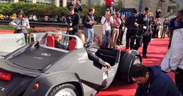 "Jay Rogers (in driver's seat) and Doug Woods drive away in the newly finished ""Strati"" electric car, which can reach a top speed of 40 mph and only has about 40 parts. (Photo courtesy of Bernard & Company)"