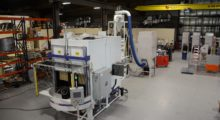 Designed for cellular manufacturing, the expanded RXS-400 Rotary-Index Twin Spindle machine utilizes a Fanuc M710 Robot that carries a bank of eight Guyson Model 900 guns mounted in a custom designed heavy duty cabinet with powered sliding door. The robot suit is custom designed to accommodate the ultimate in abrasion protection and freedom of movement, reducing the possibility of robot faults due to the suit binding on the arm. (first view)
