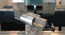 This custom press brake tool consists of a pair of upper tool holders, connected by a bar, to create a large window. The bar attaches to one of the tool holders by a pivoting hinge, and the other end is held in place by a magnetic clasp. This tool allows a closed profile to be formed around the bar and then removed by releasing the magnetic clasp, pivoting the bar outward, and easily sliding the finished product free of the tool assembly. (first view)