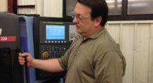 Manufacturing engineer Ian Dotson of EMC Precision keeps an eye on the machining progress of a Daewoo Lynx 220 CNC lathe cutting a transmission gear shaft made of 1-1/4 in 8620 steel with the Beyond Evolution single-sided grooving and cut-off system.