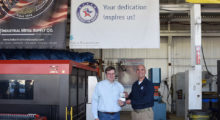 John Phillips (right), a principal at Fish & Richardson, presents Hernán Luis y Prado (left), the founder of Workshops for Warriors,  with a patent for their device that levels machines on support surfaces.